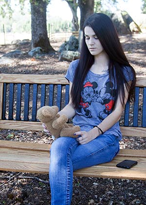 Young woman sitting on park bench looking at teddy bear