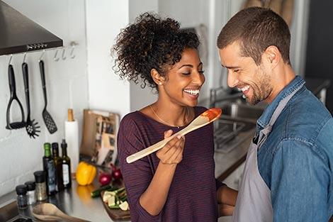 Young hopeful adoptive couple making dinner together