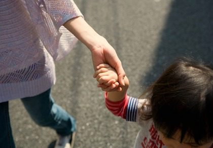 Adoptive mom holding her adopted child's hand while walking together