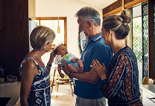Adoptive grandparents admire their grandson