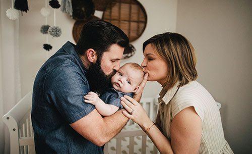 Lifetime adoptive couple kiss their infant son