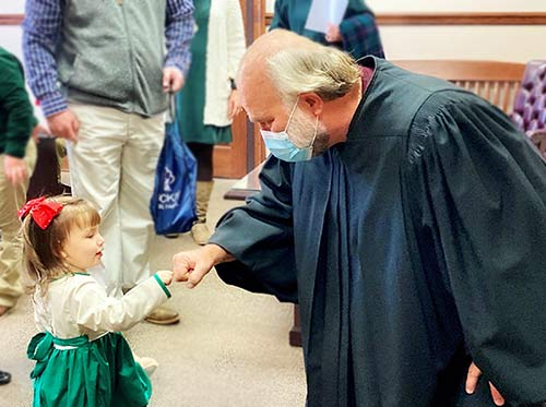 An adoptee and judge bump fists after her adoption is final