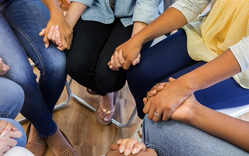 A group of women holding hands at one of the birth mother support groups