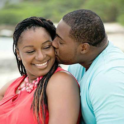An African American man gently kisses his wife on the cheek