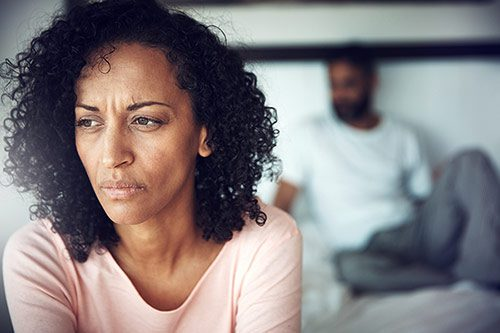Unhappy black couple in their bedroom wonder if they should move from fertility treatments to adoption
