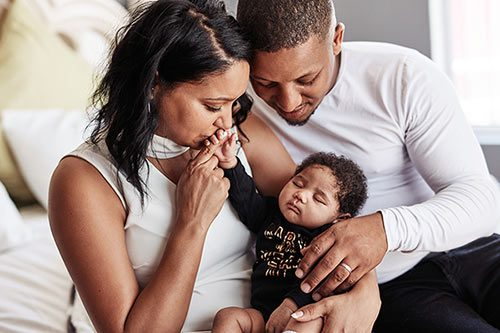 Affectionate adoptive couple who learned about adoption costs and requirements before adopting their baby girl
