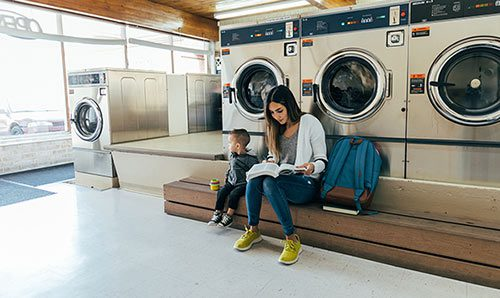 Student parent studying at laundromat