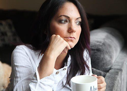 Woman in her twenties in deep thought in her living room
