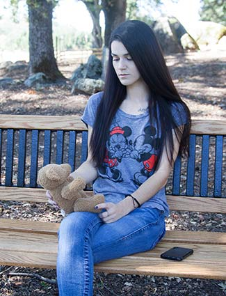 Young woman sitting on a park bench, looking down at a teddy bear