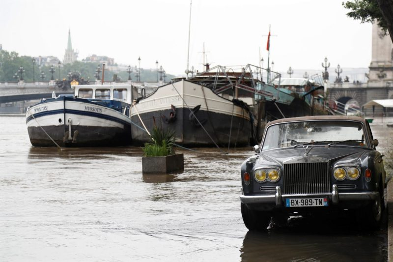A Rolls-Royce is parked as high waters causes flooding along the Seine River in Paris