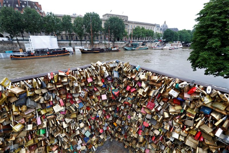 Padlocks clipped by lovers are seen in front of the flooded river-side of the River Seine in Paris, France, June 1, 2016. REUTERS/Charles Platiau