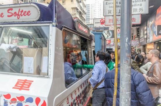 Машина с мороженым вызывает очередь на улице.
