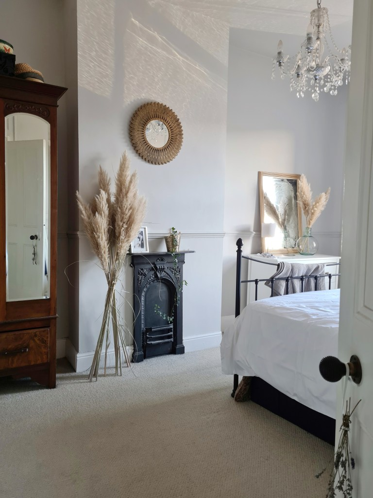 Master bedroom in a Victorian terrace with black fireplace, antique wardrobe and chest of drawers. Large pampas grass to the side of the fireplace. From a blog post about neutral paint colours in period homes by Life with Holly