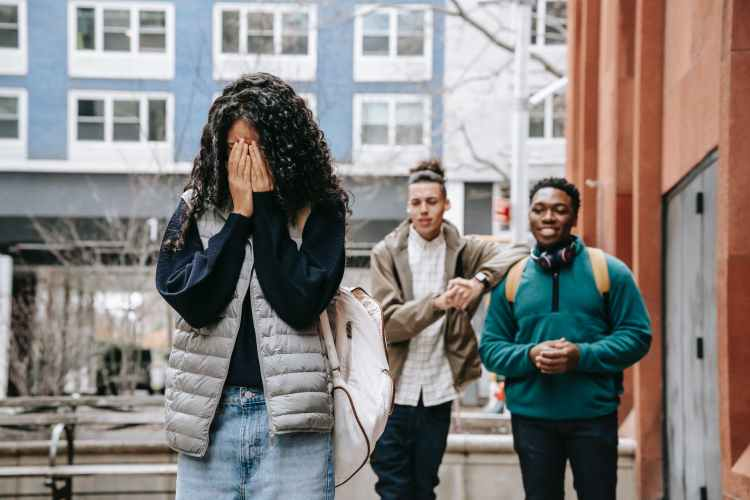 diverse male teenagers bullying anonymous lady covering face with hands