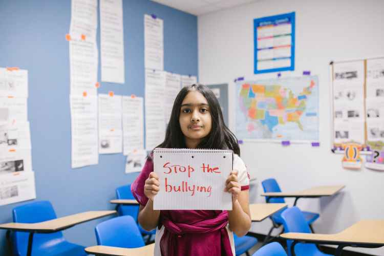 girl showing a message written in a notebook about bullying for kids