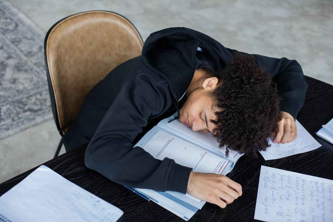 tired black man lying on opened book and homework papers