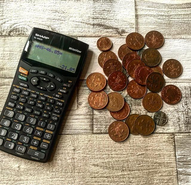 calculator and coins on a wooden background for student budgeting post