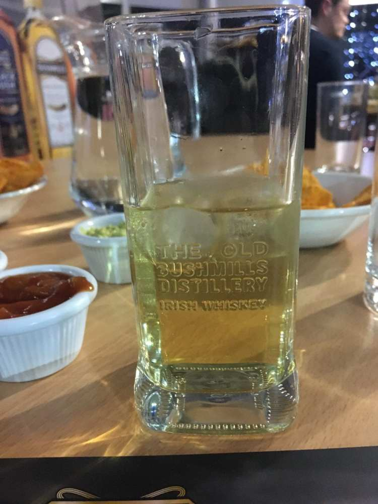 """A short Whiskey tumbler with """"The Old Bushmills Distillery Irish Whiskey"""" engraved on the glass. Inside the glass is a standard measure of Bushmills' Black Bush whiskey mixed with a sparkling apple juice"""