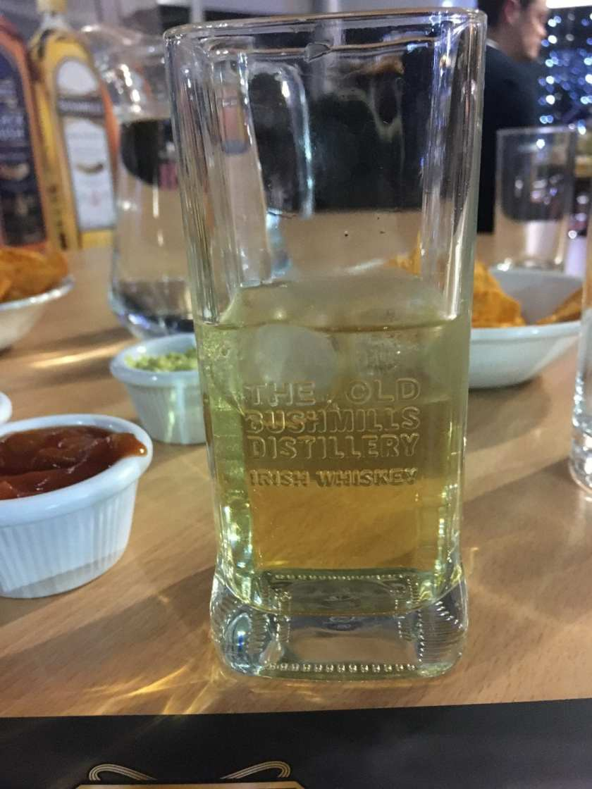 "A short Whiskey tumbler with ""The Old Bushmills Distillery Irish Whiskey"" engraved on the glass. Inside the glass is a standard measure of Bushmills' Black Bush whiskey mixed with a sparkling apple juice"