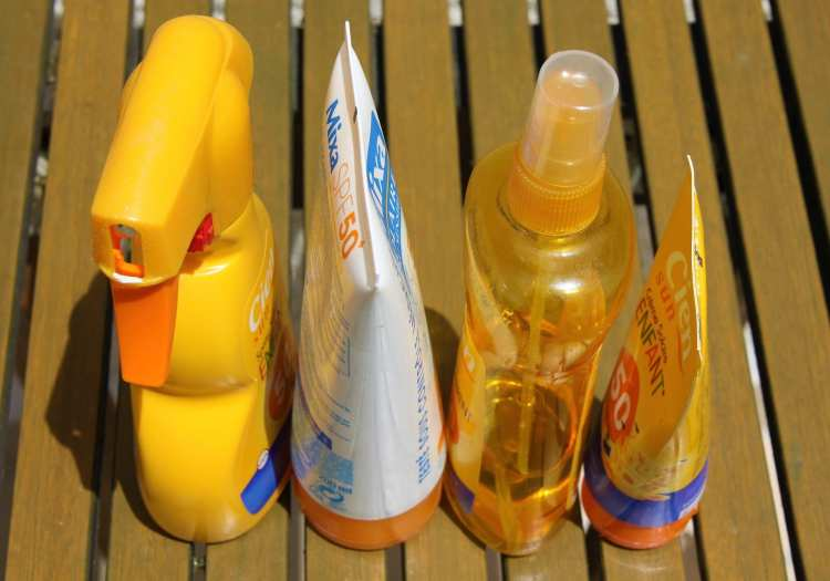 Four different sunscreen bottles in a row on decking, still needed for a home holiday