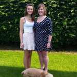 Rachel in a white dress, and me in a blue and white polka dot dress standing in the garden.