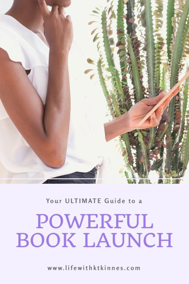 """Woman in a white shirt and back jeans holding an e-reader, as the text underneath (in black writing) states """"Your Ultimate Guide to a Powerful Book Launch"""""""