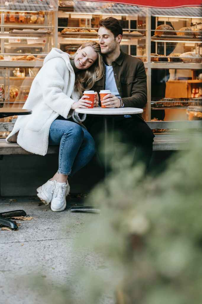 couple sitting in street cafe with cups of drink