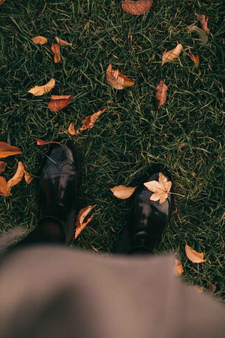 person standing on grass, autumn leaves falling down in September 2021