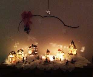 Lighted Village with Mistletoe Stick and Snowflakes Hanging Above nighttime - Life With Lorelai
