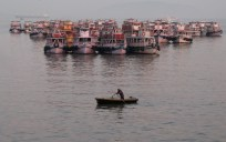 Dawn breaks over Mumbai harbor revealing a man rowing his boat, skirting the anchored ferries. The harbor opens to the Arabian Sea.
