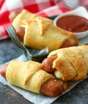 Cheesy Italian Pigs in a blanket with mozzarella wrapped in flaky dough are perfect for dipping in marinara and make a quick weeknight dinner!