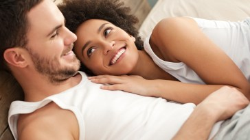 Mixed couple in bed intimacy smile smiling Why You Shouldn't Panic And Definitely Wait Before Having Sex