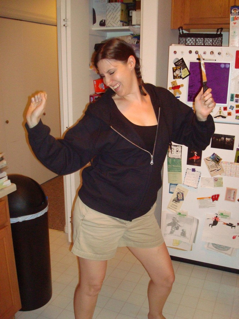 Picture of a white woman with brown hair in braids, smiling and dancing in a kitchen.
