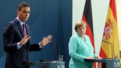 صورة رئيس الحكومة الإسبانية يقر بصعوبة التفاوض على الصندوق الأوروبي أمام المستشارة الإلمانية التي تمد يدها للاتفاق