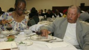 Greater Piney Grove Baptist Church members learn the ritual of placing a drop of wine for each plague.