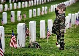 little boy saluting a soldier's grave