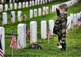 little boy saluting a soldier's grave