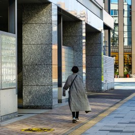 Woman walking at the entrance of a skyscraper