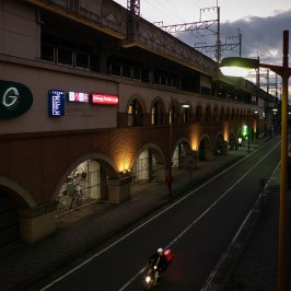 A bike on the street in front of the station at sunset