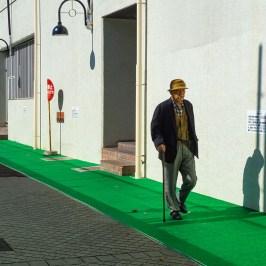 Elderly man walking behind the building