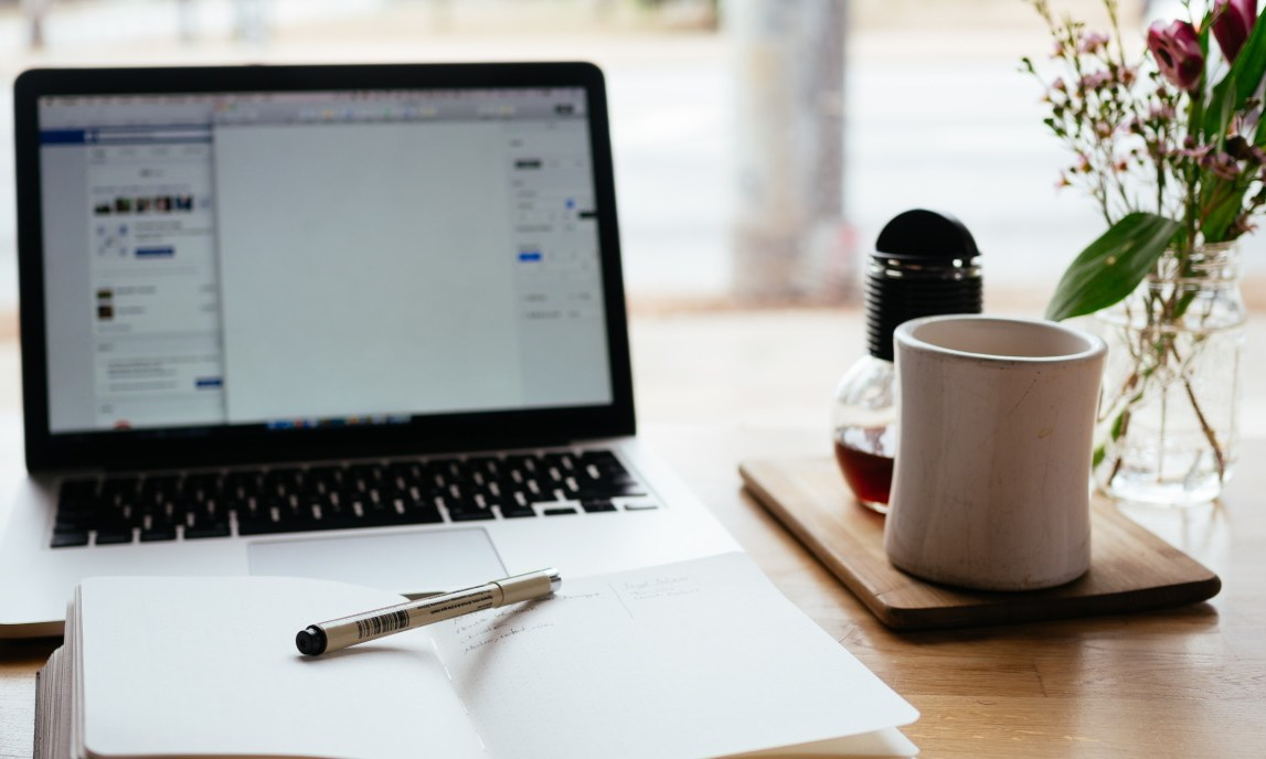 ideal blog post length | open laptop with blank notebook and pen