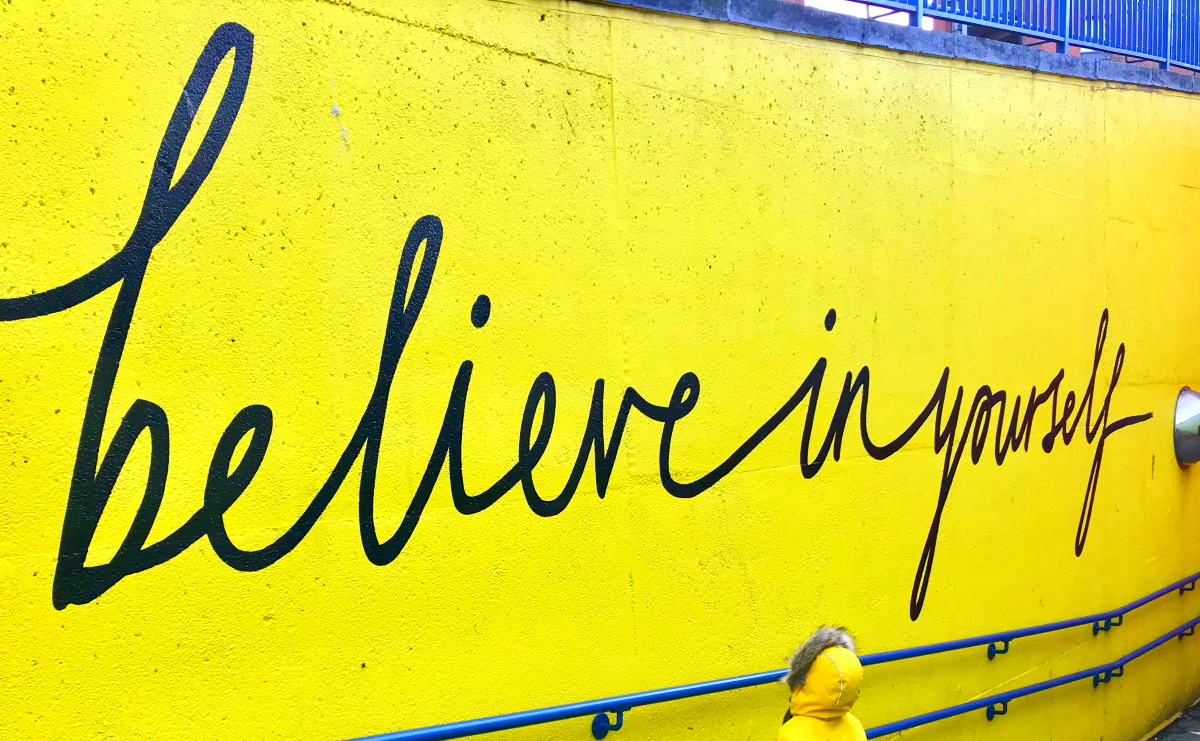 'believe in yourself' graffiti on yellow wall