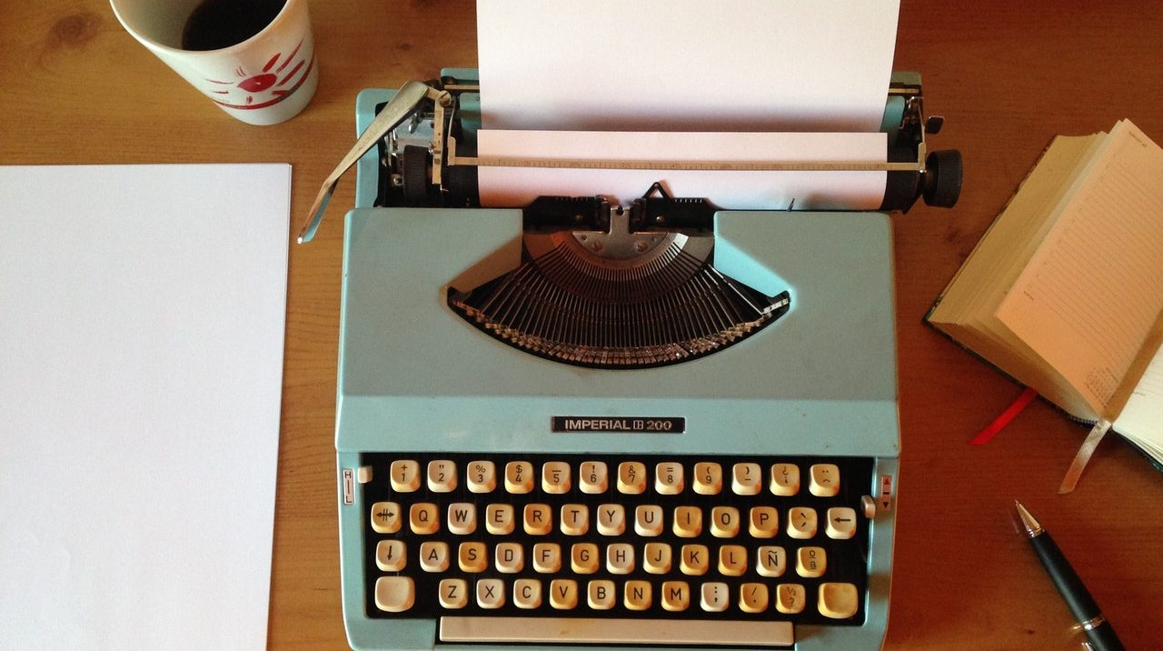 teal typewriter on desk with coffee and paper