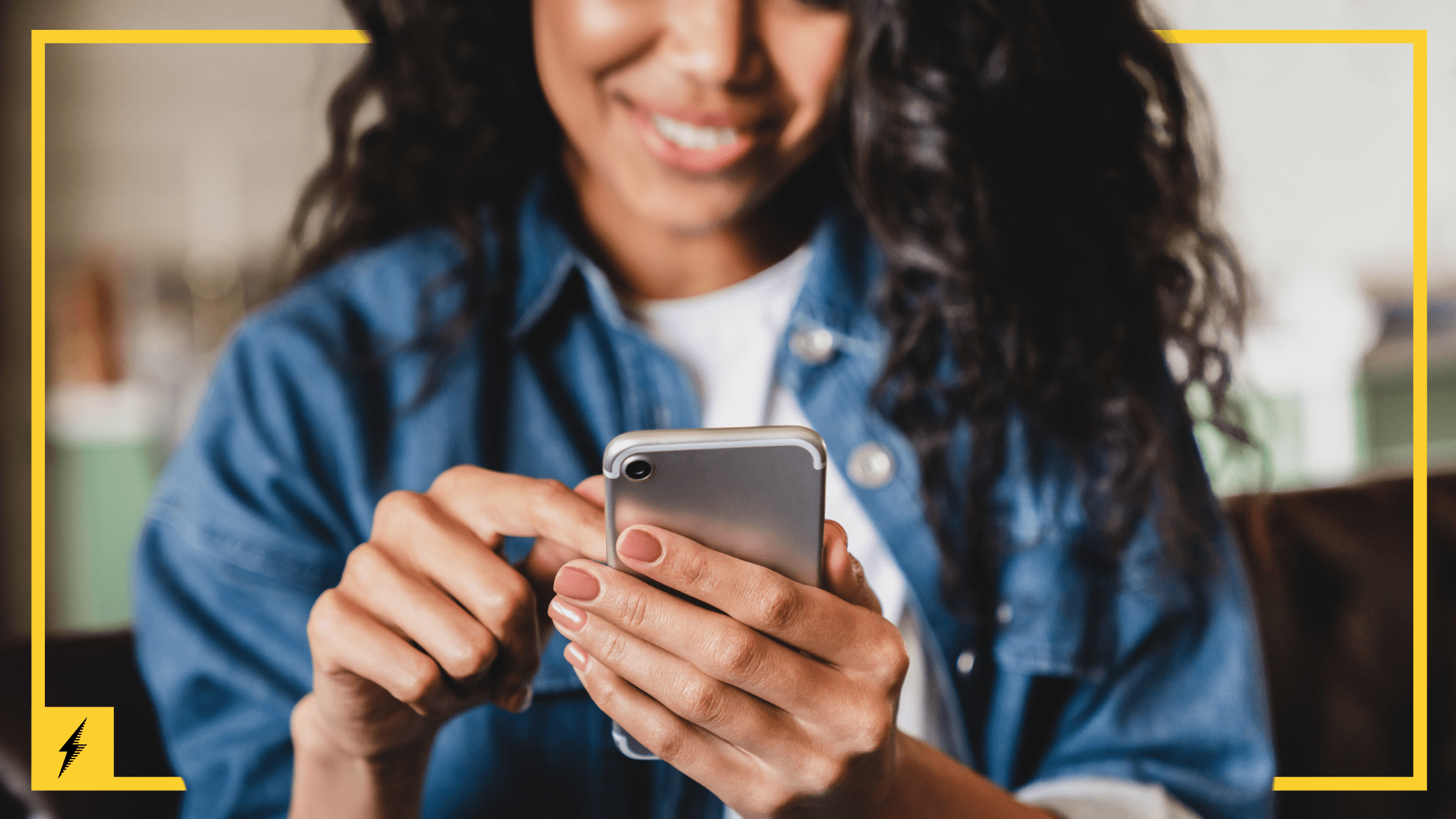 A woman smiles while using a mobile phone.