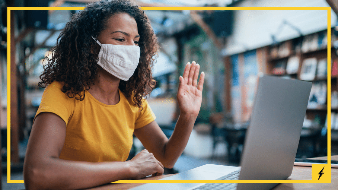 woman wearing a mask in a yellow shirt waving to her open laptop