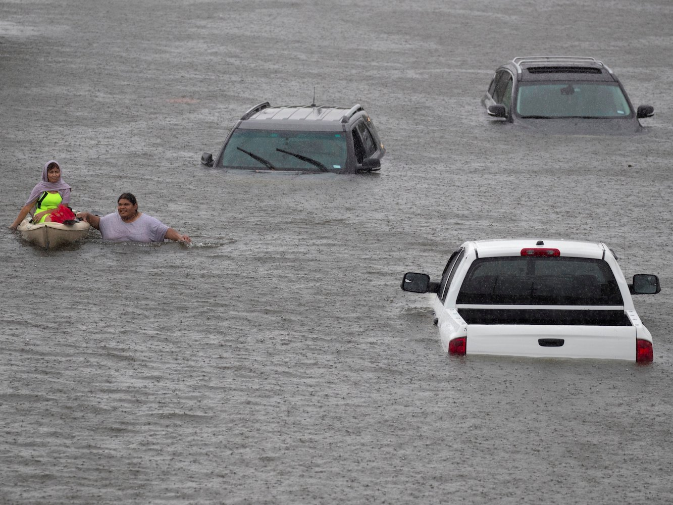 A resident of Houston  (right) rescues a stranded woman (left) from a flooded area.