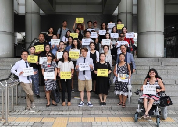 Photo of Korean adoptees with signs written in Korean to support Adam Crapser's lawsuit against Holt and Korea.