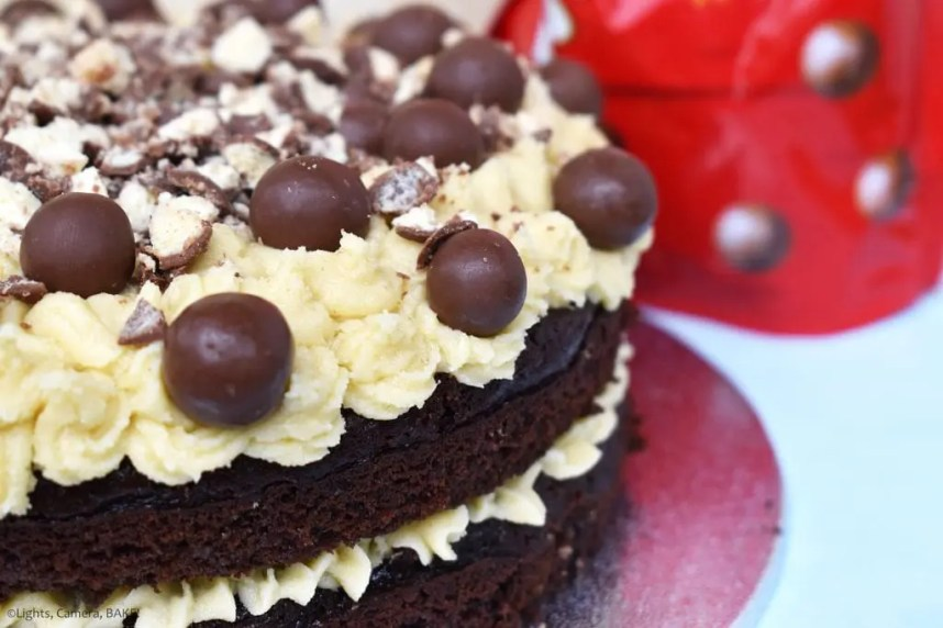 Side of a two tiered Malteser Chocolate Cake with malted buttercream middle and top with crushed Maltesers and full Maltesers. Malteser packet in the background.
