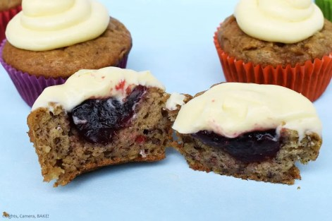 Raspberry Banana Cake Cupcakes with Cream Cheese Icing chopped in half with the raspberry jam filling.