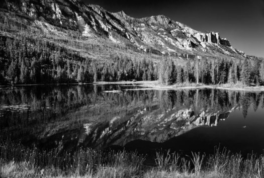 Mountains reflect in Swamp lake along the Chief Joseph Scenic Byway. The Byway runs between Cody, Wyoming and the southern end of the Beartooth Highway.